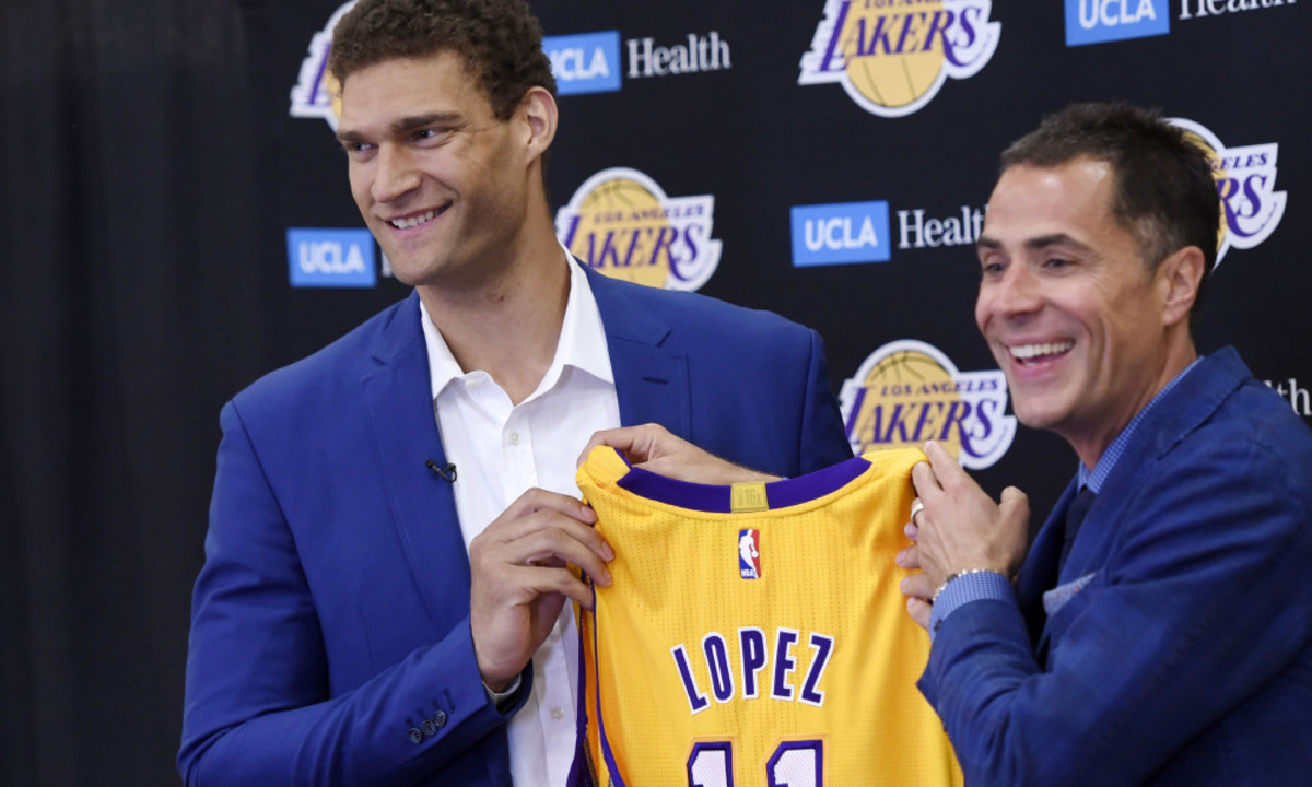 Brook Lopez, left, a new member of the Los Angeles Lakers, holds up his jersey with Lakers general manager Rob Pelinka during a news conference at Toyota Sports Center in El Segundo, Calif., on Wednesday, June 28, 2017. (AP Photo/Chris Pizzello) ORG XMIT: CACP301