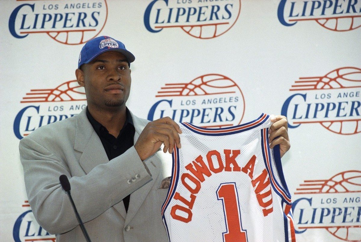 Michael Olowokandi, the first pick in Wednesday's NBA draft, holds a Los Angeles Clippers jersey during a news conference in Los Angeles on Thursday, June 25, 1998. Olowokandi, a 7-foot-1 Nigerian who grew up in England and has been playing competitive basketball for only three years, played last season at Pacific University. (AP Photo/Nick Ut)