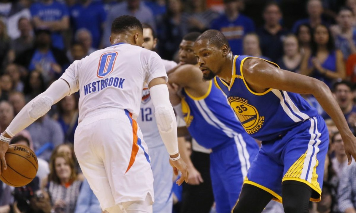 Golden State Warriors forward Kevin Durant (35) defends as Oklahoma City Thunder guard Russell Westbrook (0) dribbles in the first quarter of an NBA basketball game in Oklahoma City, Saturday, Feb. 11, 2017. (AP Photo/Sue Ogrocki) ORG XMIT: OKSO111