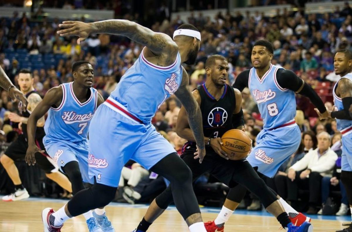 Feb 26, 2016; Sacramento, CA, USA; Los Angeles Clippers guard Chris Paul (3) dribbles the ball between Sacramento Kings guard Darren Collison (7), center DeMarcus Cousins (15), and forward Rudy Gay (8) during the first quarter at Sleep Train Arena. Mandatory Credit: Kelley L Cox-USA TODAY Sports